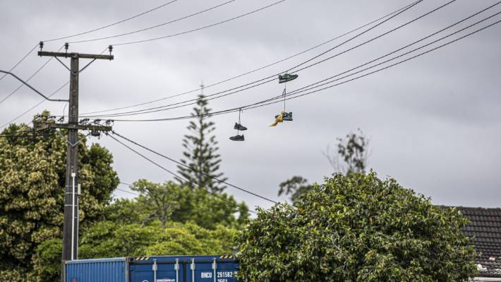 Shoes hang above the homes at the centre of the trouble in Lancaster Rd, bearing the yellow colours of the Tribesmen and Killer Beez gangs (file photo).