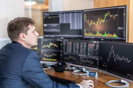 white-man-sitting-trading-computer-desk-trading-system-robo-advisor-roboadviser-finance