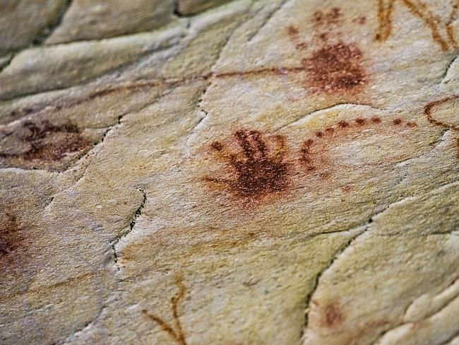 Paintings of hands made by blowing red ochre pigment.