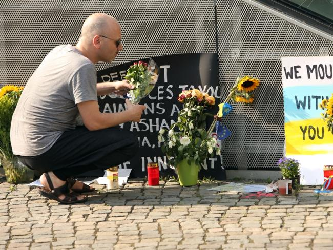A visitor places flowers at a temporary memorial for the victims in Berlin.