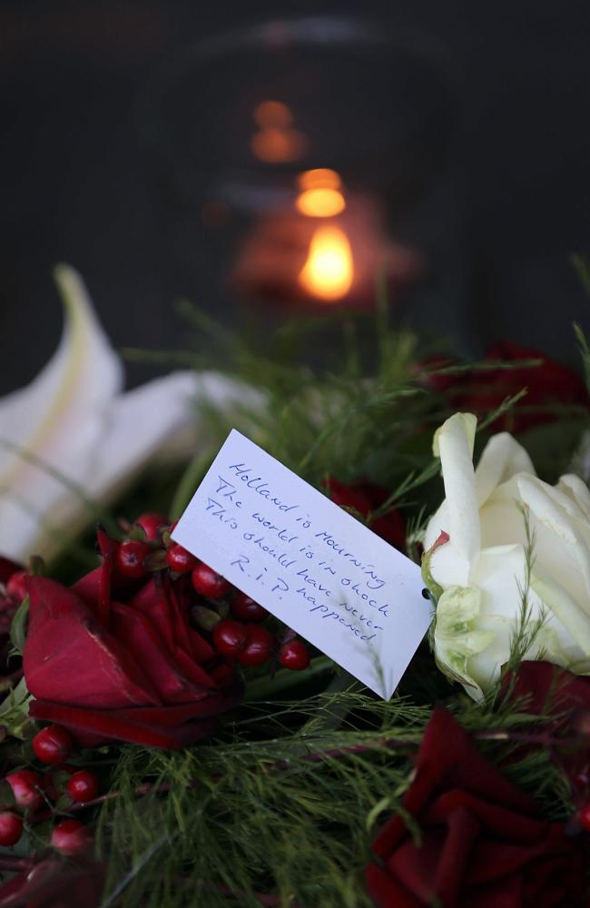 A candle burns nex to flowers at the entrance to Schiphol Airport.