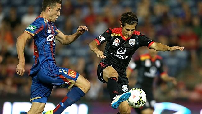 Pablo Sanchez controls the ball for Adelaide under pressure from Scott Neville.