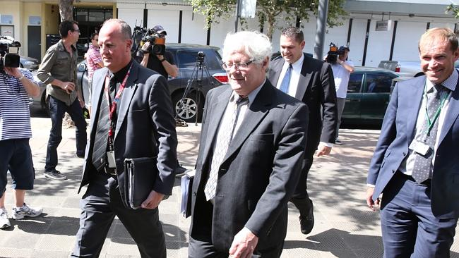 Commonwealth DPP prosecutor Michael Allnut, centre, arriving at Fairfield court today whe