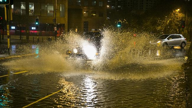 A Jeep splashes through flooding at the intersection of Eddy and Pitt streets in Sydney's