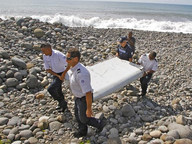 Investigation begins ... Authorities move the debris from the rocky beach. (AP Photo/Luca