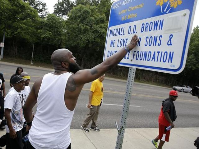 Lasting legacy ... Michael Brown Sr. stops to touch an adopt-a-highway sign with his son'