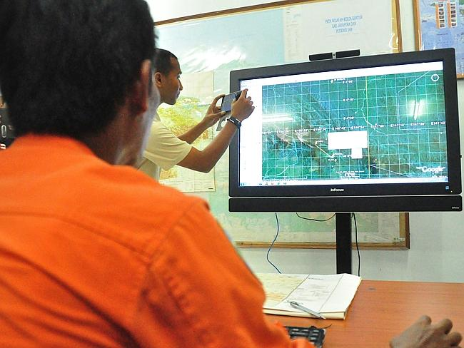 Indonesia's National Search and Rescue personnel view a terrain map in Jayapura in the ea