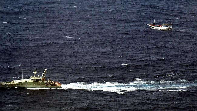 An Australian Navy vessel sailing alongside a wooden boat carrying up to 180 asylum seekers on the waters off Christmas Islan...