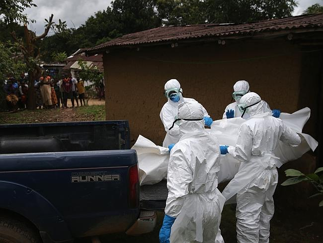 A burial team from the Liberian Red Cross carries the body of an Ebola victim from his ho