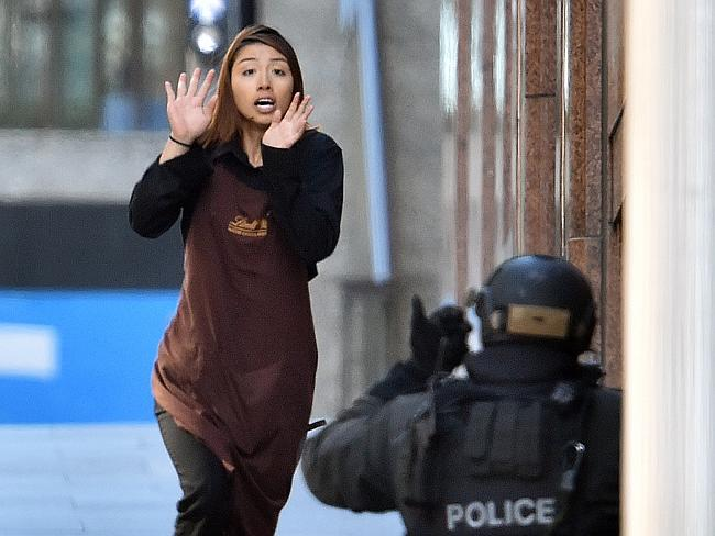 One of the hostages runs towards police from Lindt cafe in the central business district