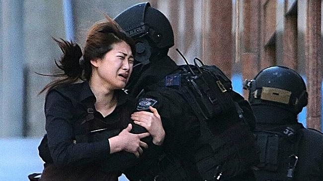 A hostage runs to an armed tactical response police officers for safety after she escaped