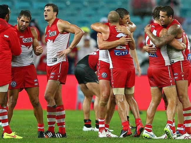 Relief: Swans players celebrate their come-from-behind victory against Essendon in their