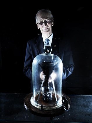 Professor John Mainstone with the Pitch Drop Experiment. [Picture: Adam Knott Source: The Australian]