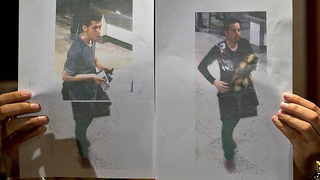 Revealed ... a Malaysian police official displays photographs of the two men who boarded