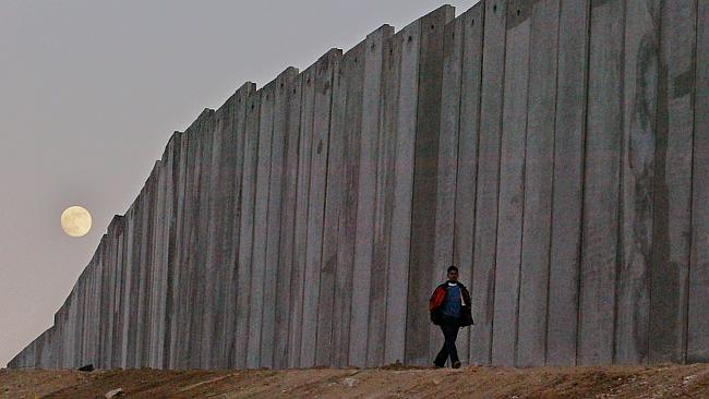 A Palestinian man walks next to the separation barrier between the West Bank and Jerusale