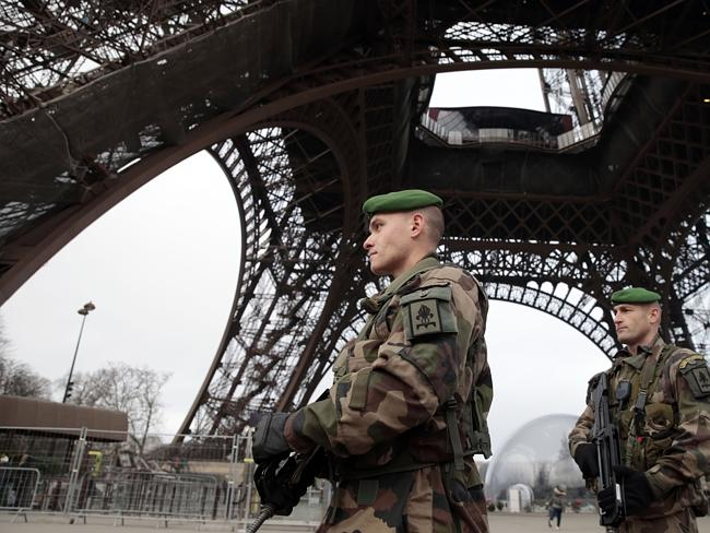 French soldiers patrol the Eiffel Tower in Paris as the capital was placed under the high