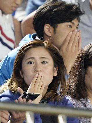 In shock ... Japanese soccer fans react to a strong earthquake as they watch a match in H