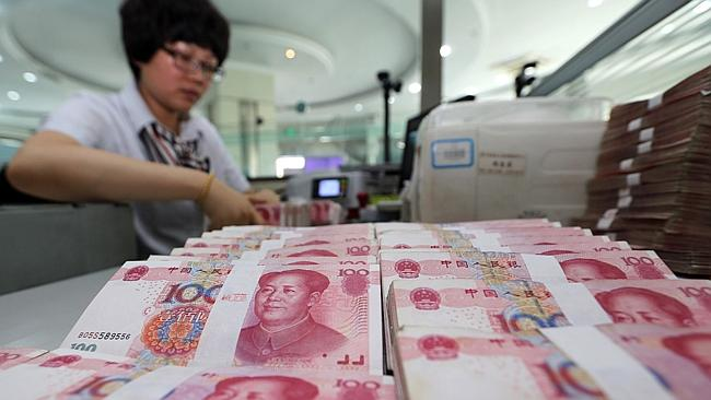 A teller counts yuan banknotes in a bank in Lianyungang, east China's Jiangsu province. A