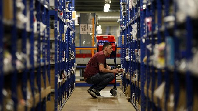 An employee selects goods from storage units ahead of packaging for delivery at Amazon.co