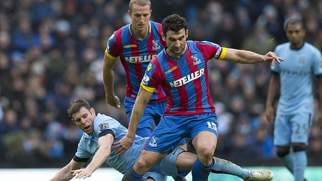 Manchester City's James Milner, bottom, fights for the ball against Mile Jedinak.