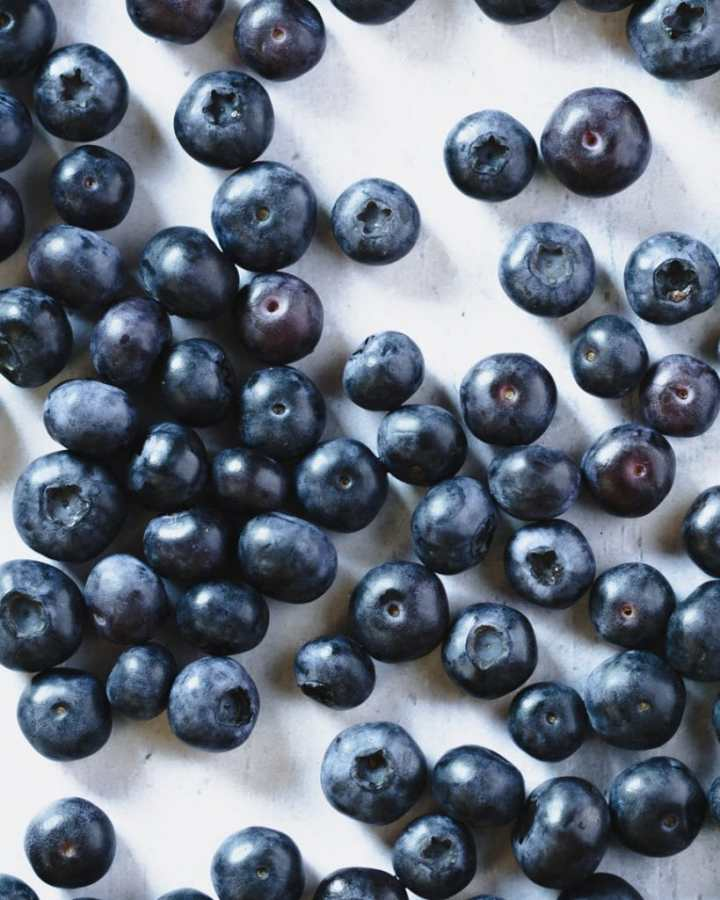 fresh blueberries viewed topdown on light blue background