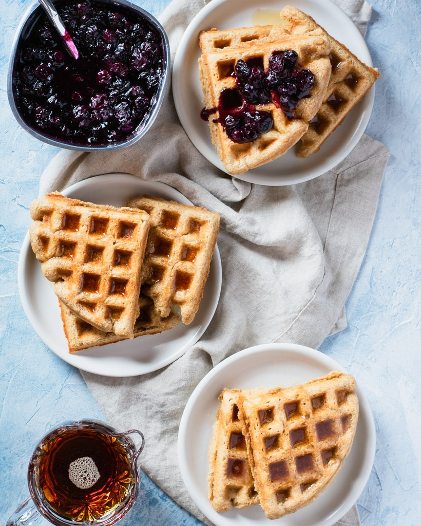 3 plates of waffles with blueberry lemon cardamom compote