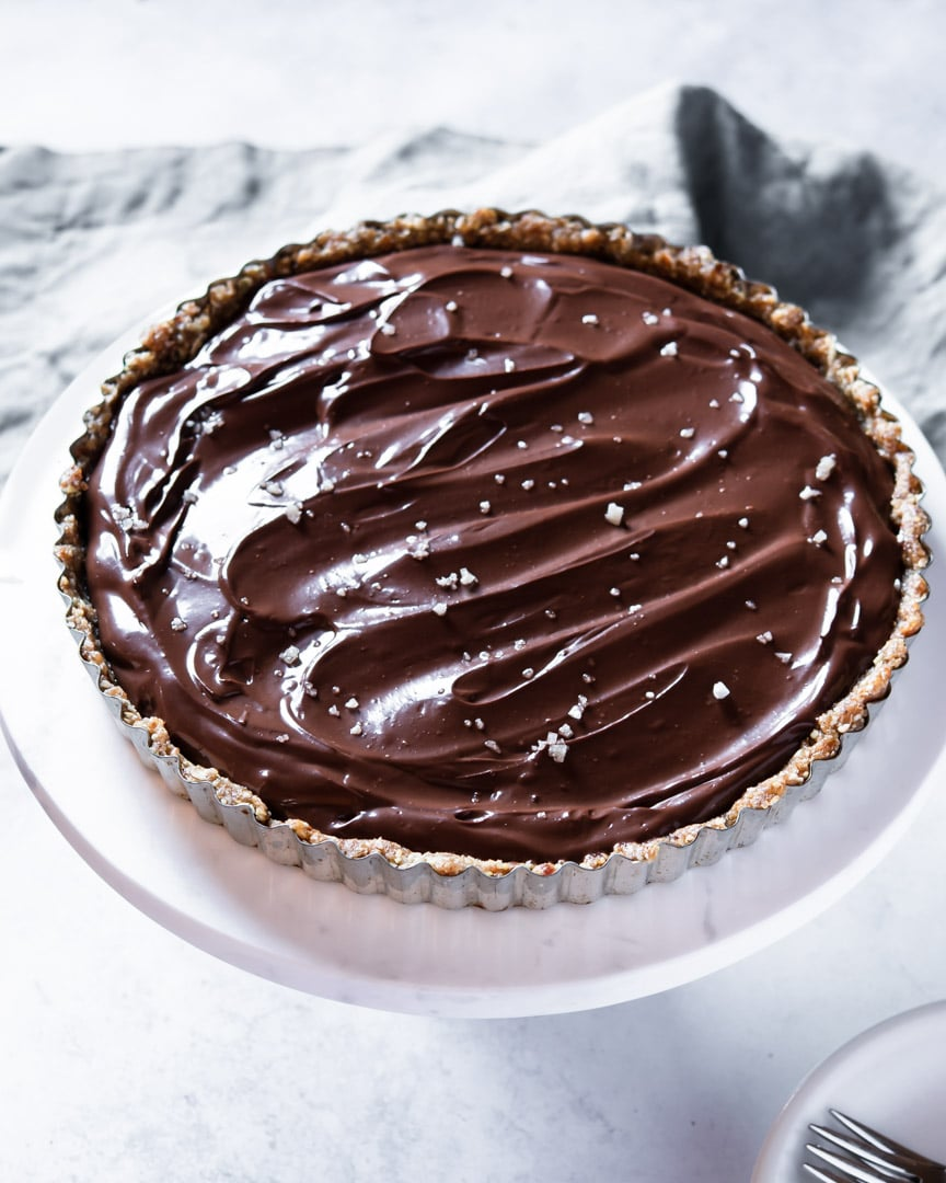 chocolate tart with flaked sea salt on top on marble cake stand