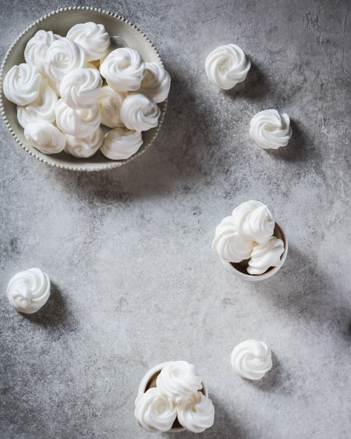 aquafaba meringue in large bowl and two small bowls on grey background