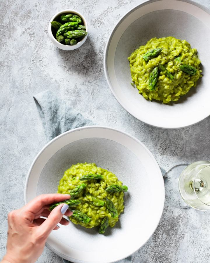 bowls of asparagus risotto with hand placing asparagus