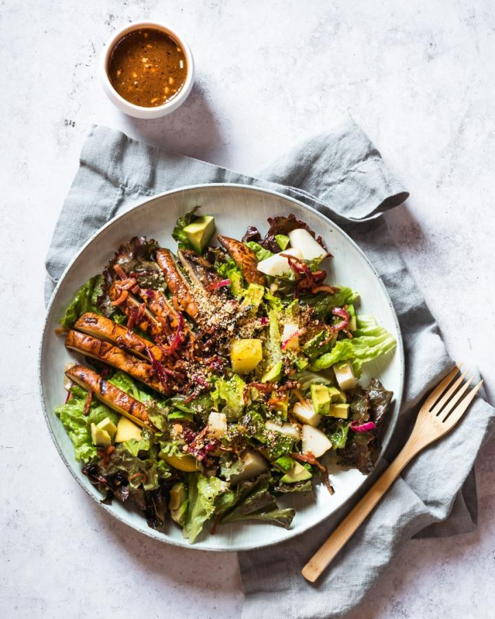 avocado, portobello, and pear salad on plate with dressing and fork