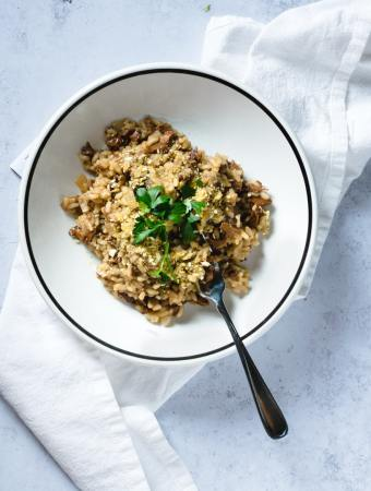 wild mushroom risotto in white bowl with fork on white napkin
