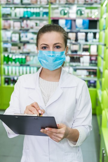 Woman pharmacist checking medication list in a pharmacy