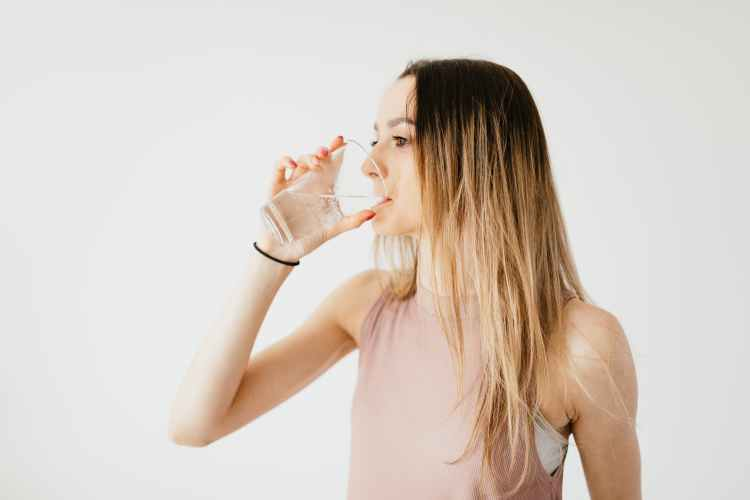 young woman drinking glass of cold pure water