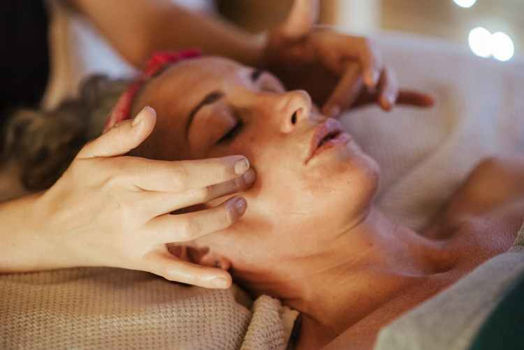 lady enjoying face massage from masseur in spa