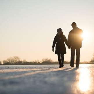 Image of couple walking into the sunset during golden hour
