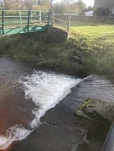 A gurgling stream and a green bridge.