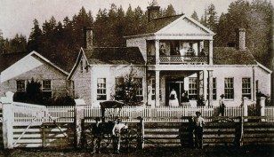 1880's image of the Sam Brown House with family members on the porch and balcony