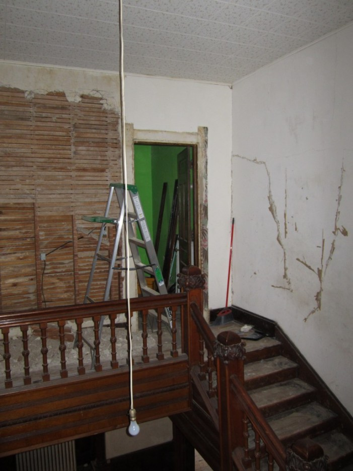 We have started to remove the plaster from the wall built in the 1920s when the Cross House was converted to apartments. The wall was created so that two kitchens could be installed, one for each of the two adjacent studio apartments (former bedrooms). When the house was converted into a motel in the 1940s, the kitchens were removed and two bathrooms built in their place. Yet later, one bath was removed, and the space converted to a small bedroom (with bath). The door to this bedroom is seen in the image.