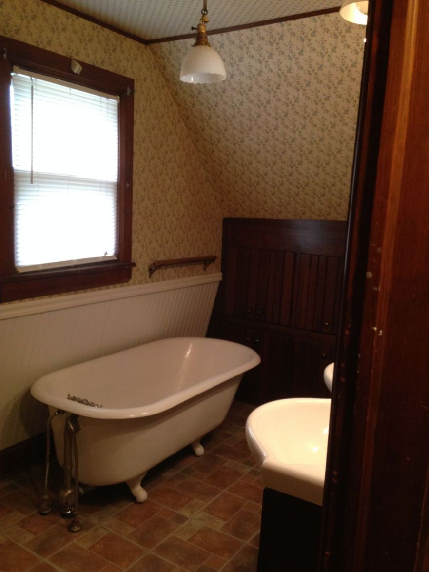 The upstairs bath. The image looks distorted; it is not. The white breadboard is set at an angle to create more room for the tub.