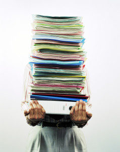 ca. 2003 --- Businessman Carrying Pile of Files --- Image by © Darama/CORBIS