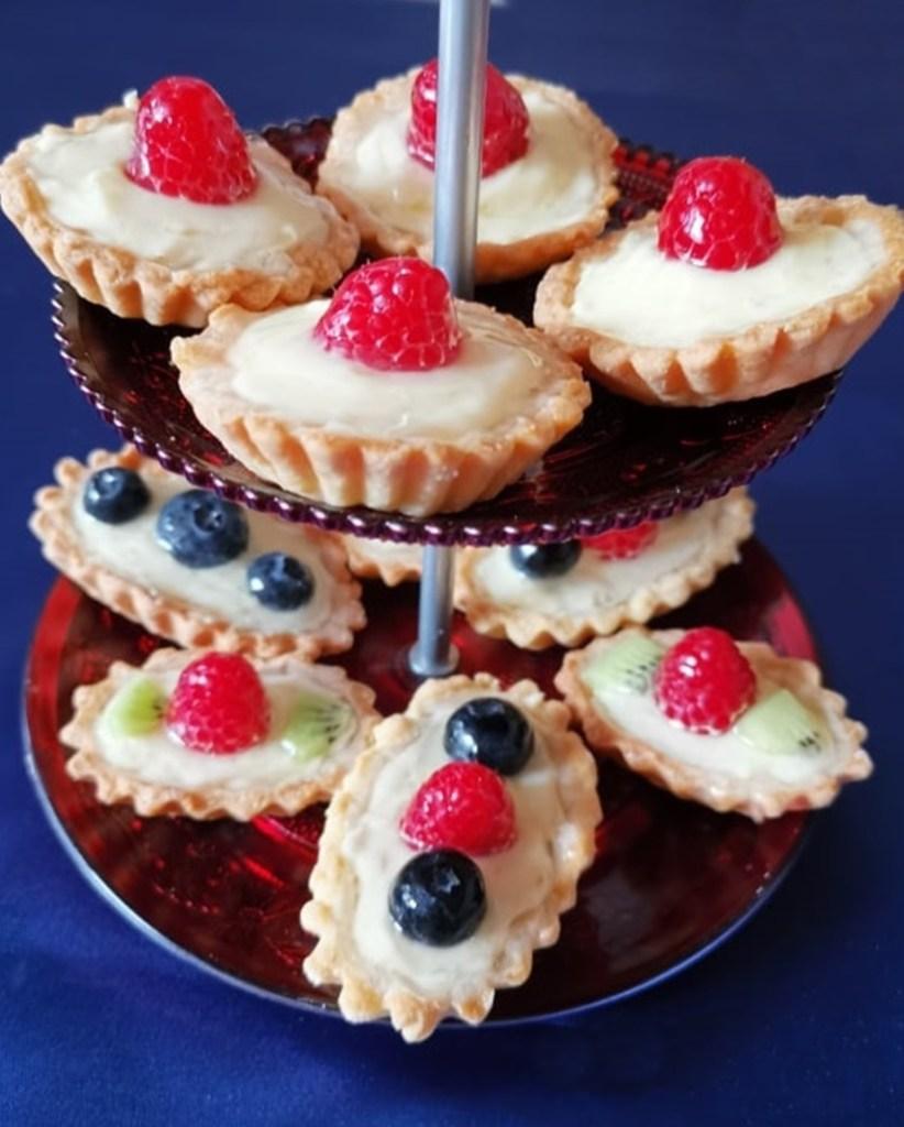 Mini tarte cu vanilie și fructe pe un platou etajat