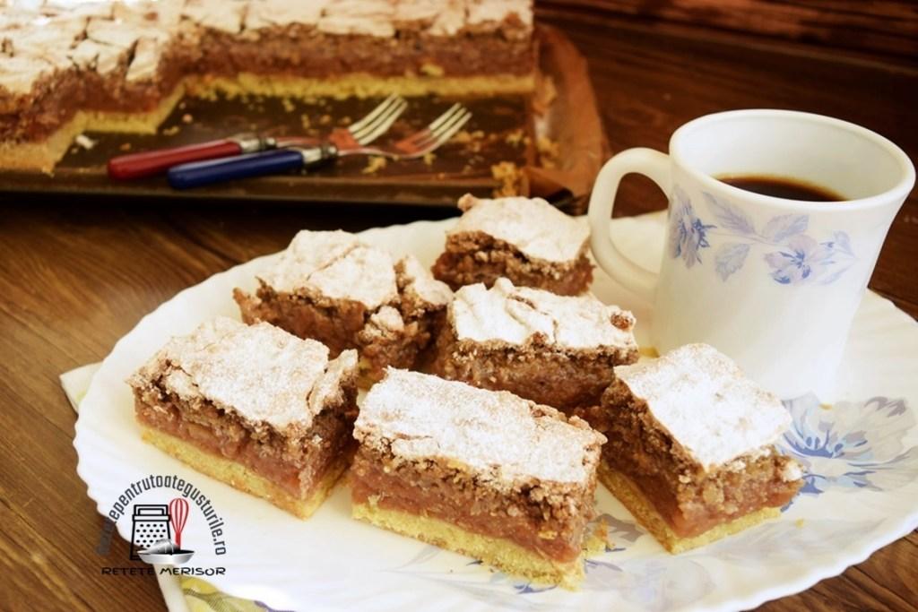 Porții din prăjitură cu mere și bezea cu nucă, pe un platou, alături de o cană cu cafea