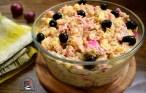Salată de cartofi cu ton file și ceapă roșie marinată, castraveciori acri, ardei copți și maioneză, decorată cu măsline