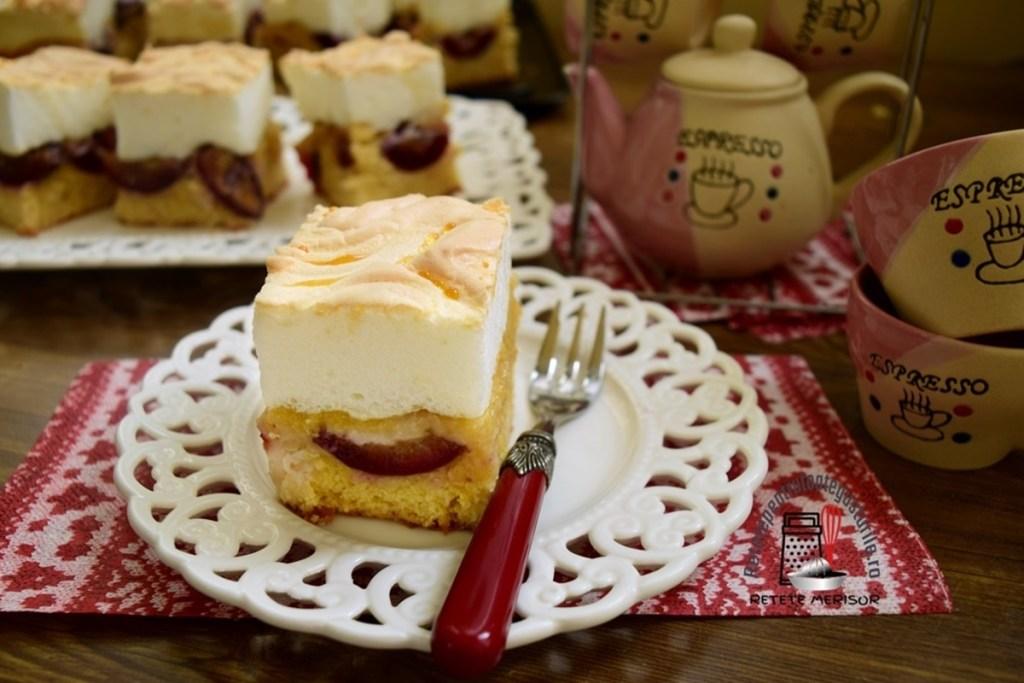 Porție de prăjitură cu prune și bezea pe o farfurie albă dantelată