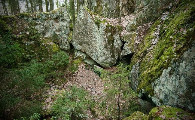 Luolan piha-aukio - sisäänkäynti alavasemmalla