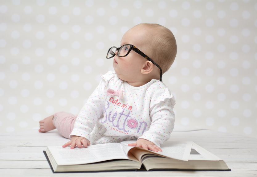 38747765 - funny portrait of a cute baby girl in glasses lying over a big book