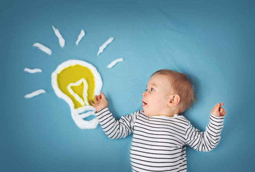 53648511 - one year old boy with a bulb on blue background. child with an idea