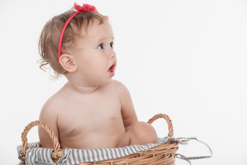 Cut little baby girl in red hoop sitting in basket. Looking away