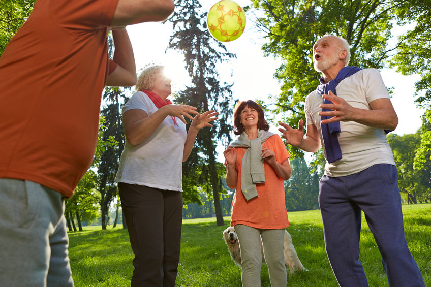 33552101 - happy group of senior people playing with a ball in a park