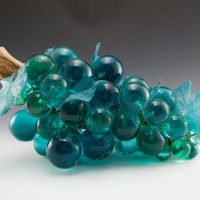 Awesome ocean blue colors. Some are lighter and some are darker blues. The giant Lucite grapes are mounted by wire to the polished real driftwood log. Thick plastic leaves are weaved throughout the grapes.